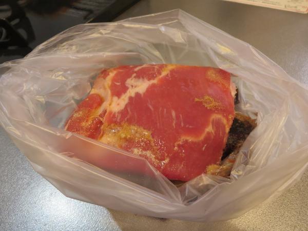 ポリ袋に入れた豚バラ肉を調味料で漬け込む