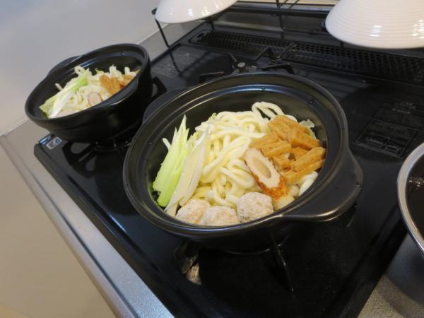 土鍋に鍋焼きうどんの具材を入れる